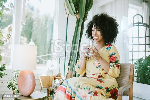 A happy young adult woman enjoys time at her home, the house interior well designed and decorated with an assortment of interesting plants.
