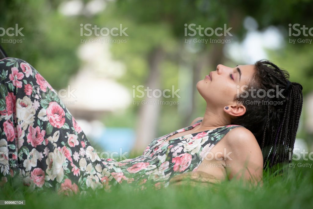 Young Woman relaxes lying on the grass - foto stock