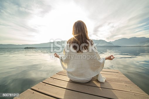 Young woman relaxes on lake pier, exercises yoga. Beautiful Autumn day in Italy.