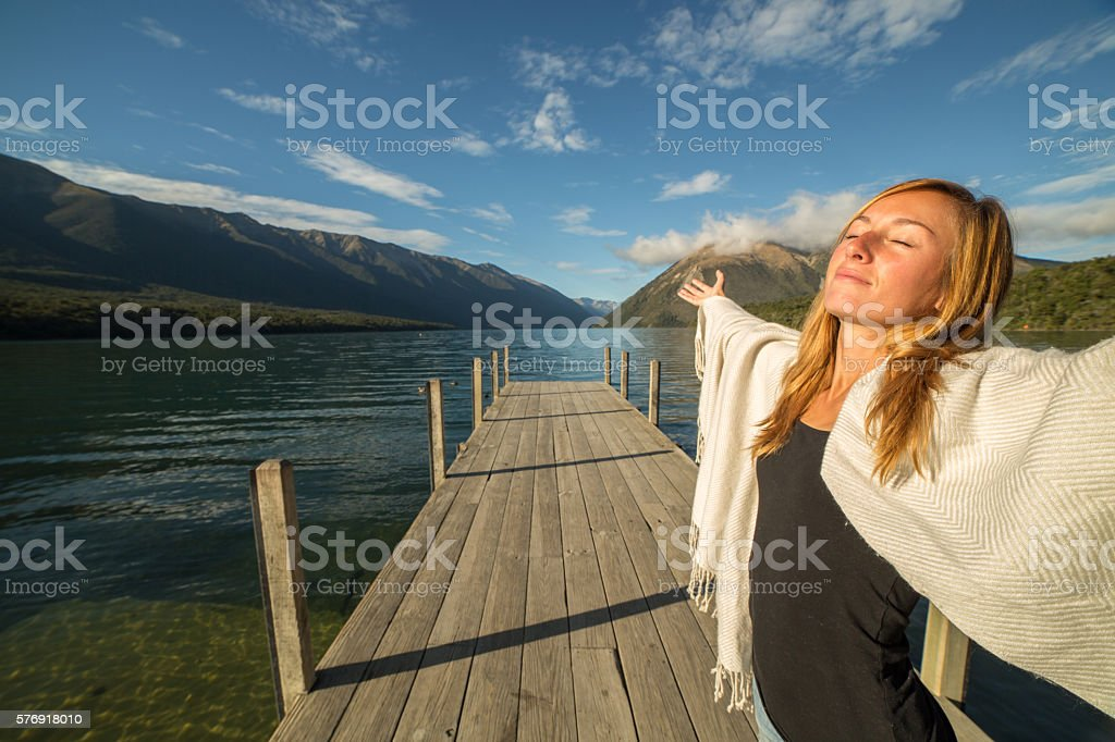 Young woman relaxes on lake pier, stands arms outstretched stock photo