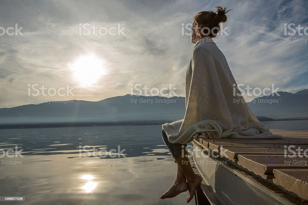 Young woman relaxes on lake pier, watches sunset. Beautiful Autumn...