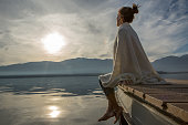 Young woman relaxes on lake pier, watches sunset. Beautiful Autumn day in Italy.