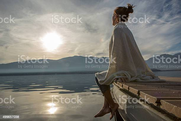 Photo of Young woman relaxes on lake pier with blanket, watches sunset