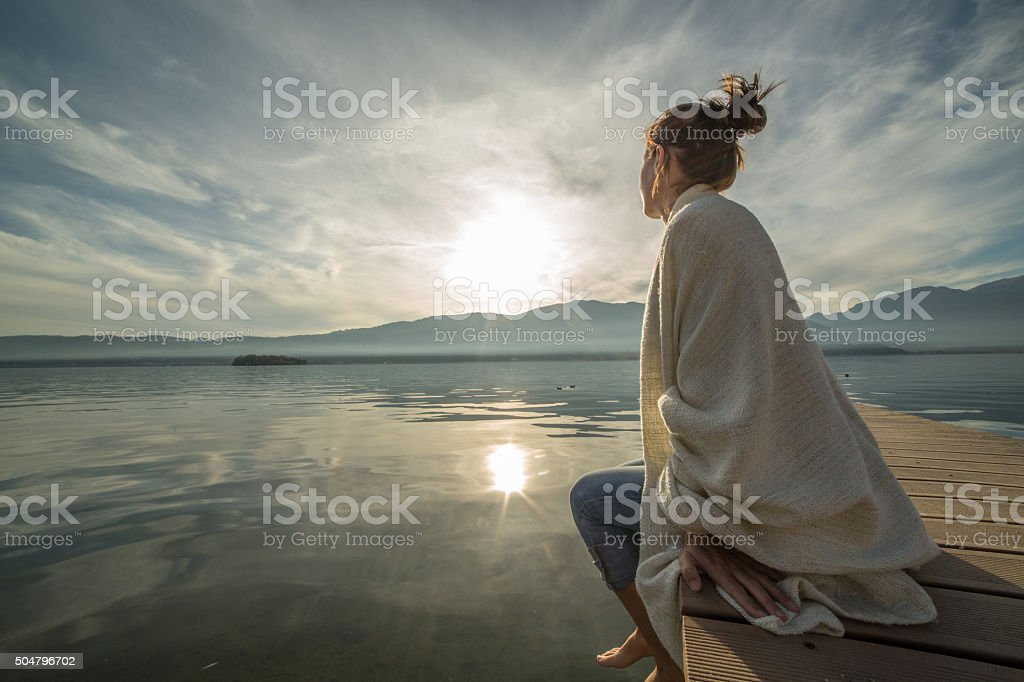 Young woman relaxes on lake pier with blanket, watches sunset stock photo