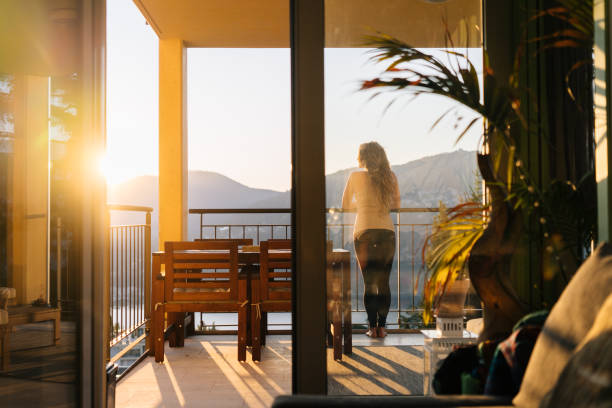 Young woman relaxes on patio at sunrise stock photo