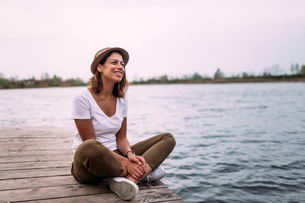 ung kvinna slappnar av på kanten av en träbryggan. - flod vatten brygga bildbanksfoton och bilder