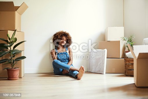Full length of young woman sitting on floor in new house. Portrait of happy female is relaxing amidst moving boxes. She is wearing bib overalls.