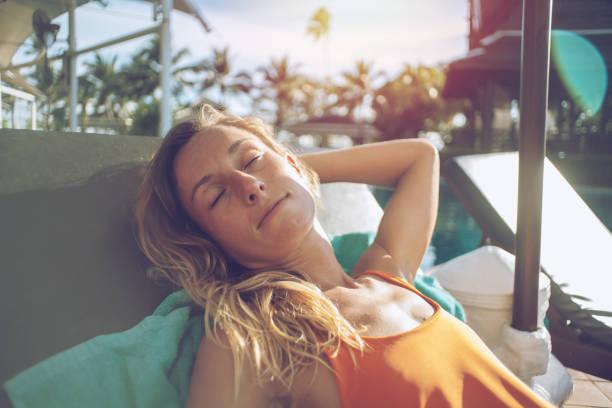 Junge Frau entspannen und Sonnenbaden auf der Liege am Pool im tropischen Klima in Asien. Menschen-Ruhe-Zen-Haltung-Konzept – Foto