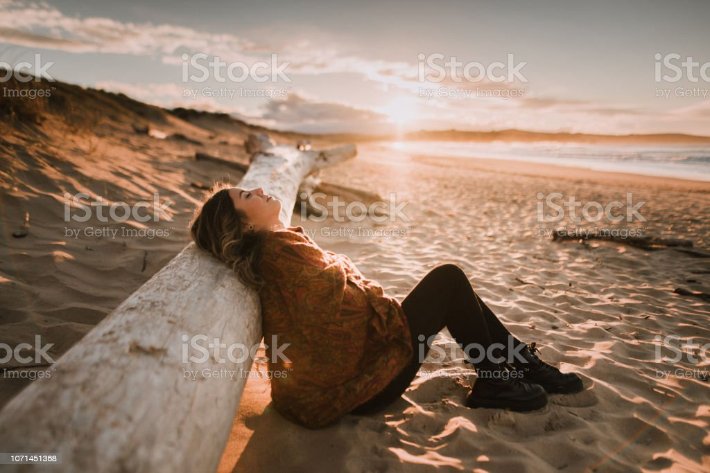 Young woman sitting and relaxing at a beach at sunset in winter