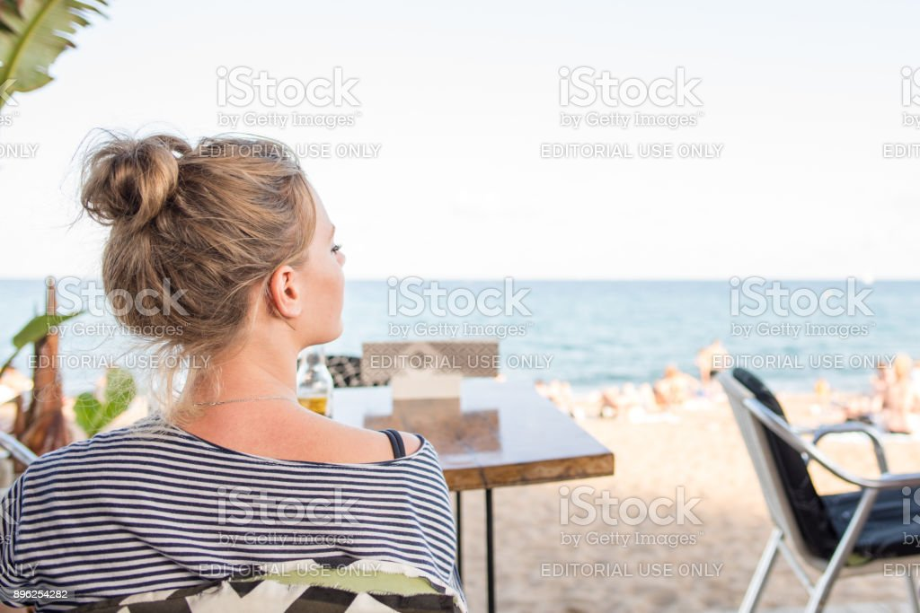 Young woman relaxing at a seaside bar  in Barceloneta, Barcelona stock photo