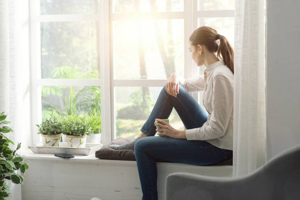 Junge Frau entspannt zu Hause neben einem Fenster und einer Tasse Kaffee – Foto