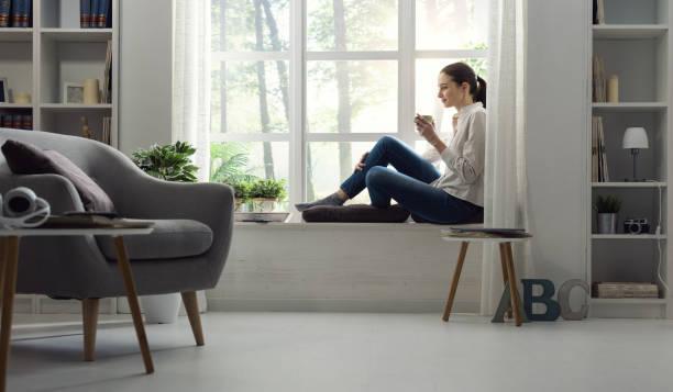 Mulher jovem em casa relaxando ao lado de uma janela e tomando um copo de café - foto de acervo