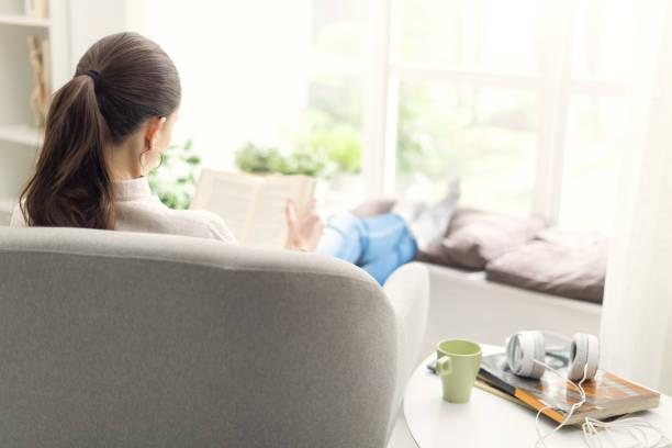 Jovem mulher relaxante em casa ao lado de uma janela, ela está sentado na poltrona e lendo um livro - foto de acervo