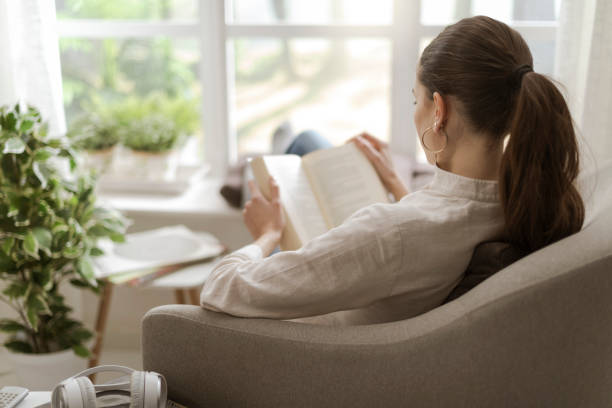 Junge Frau, die zu Hause einen Fensterplatz entspannend, sie sitzt auf dem Sessel und ein Buch zu lesen – Foto