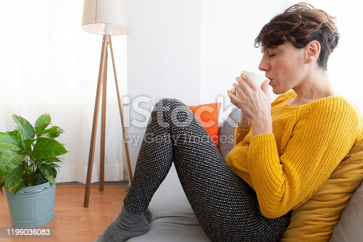 909062786 istock photo Young woman relaxing at home 1199036083