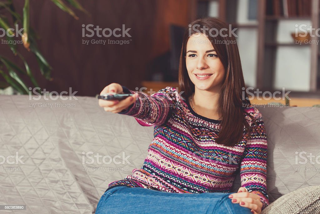 Young woman relaxing at home, watching television stock photo