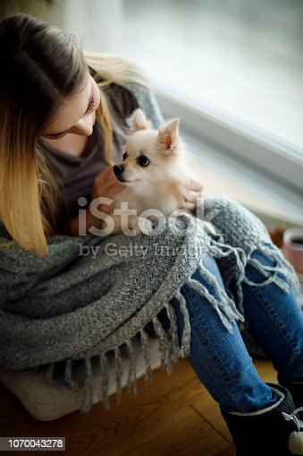 istock Young woman relaxing at home with her dog 1070043278