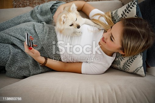 483426960istockphoto Young woman relaxing at home with her dog 1138653755