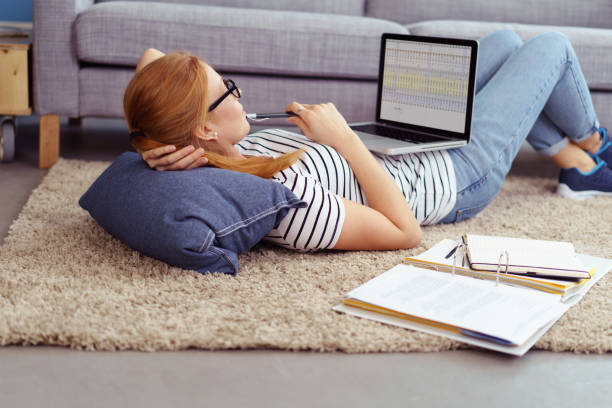 Young woman relaxing at home working stock photo
