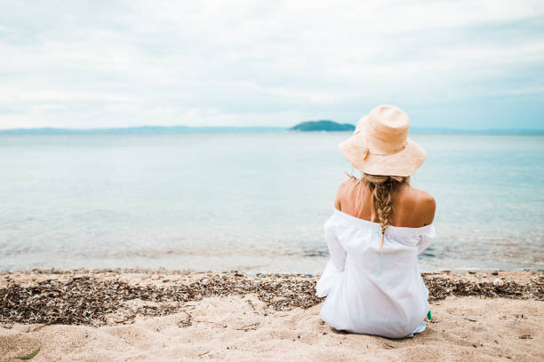 Young woman relaxing at the beach and enjoying the view stock photo