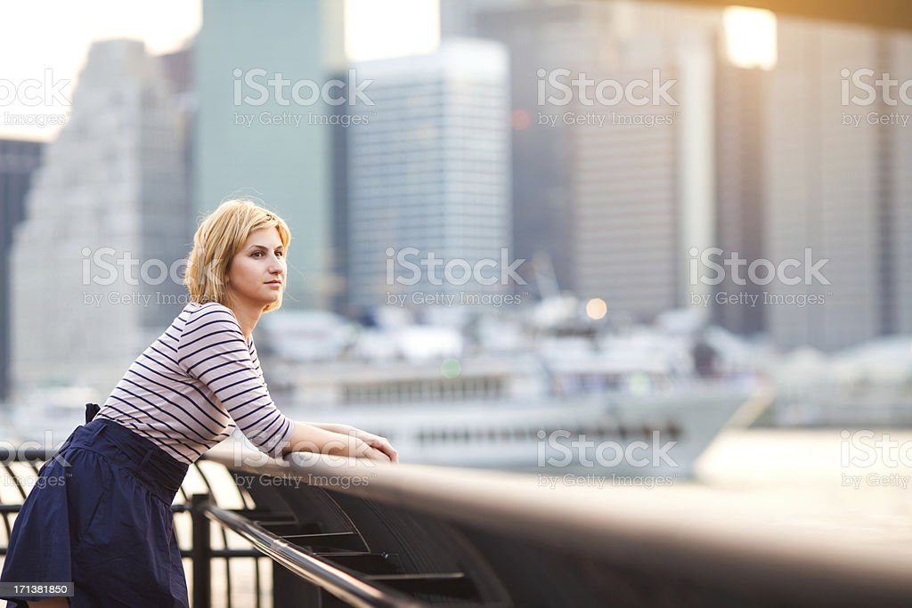 Young woman relaxing by East River in NYC royalty-free stock photo