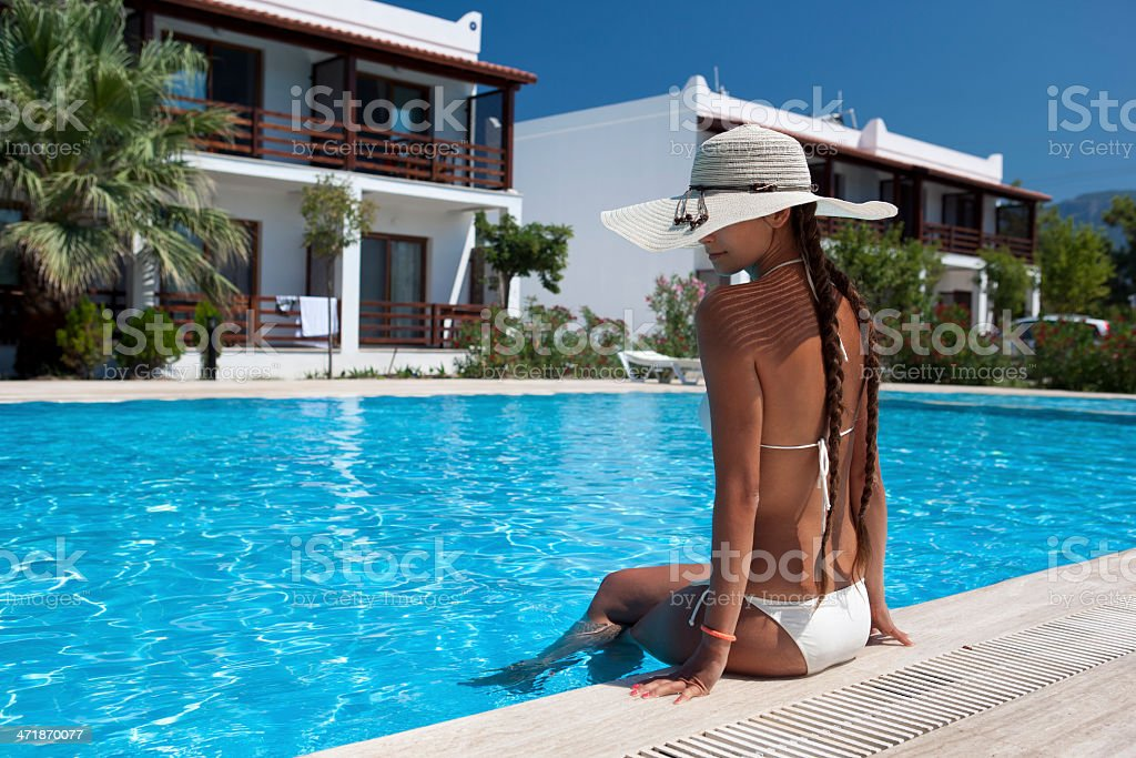 Young woman relaxing by the pool stock photo