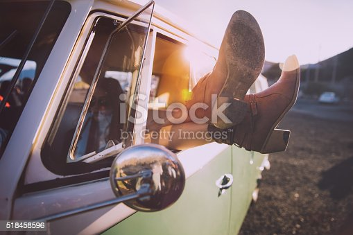 Young woman relaxing by crossing legs out of the window of a nice vintage van on sunset
