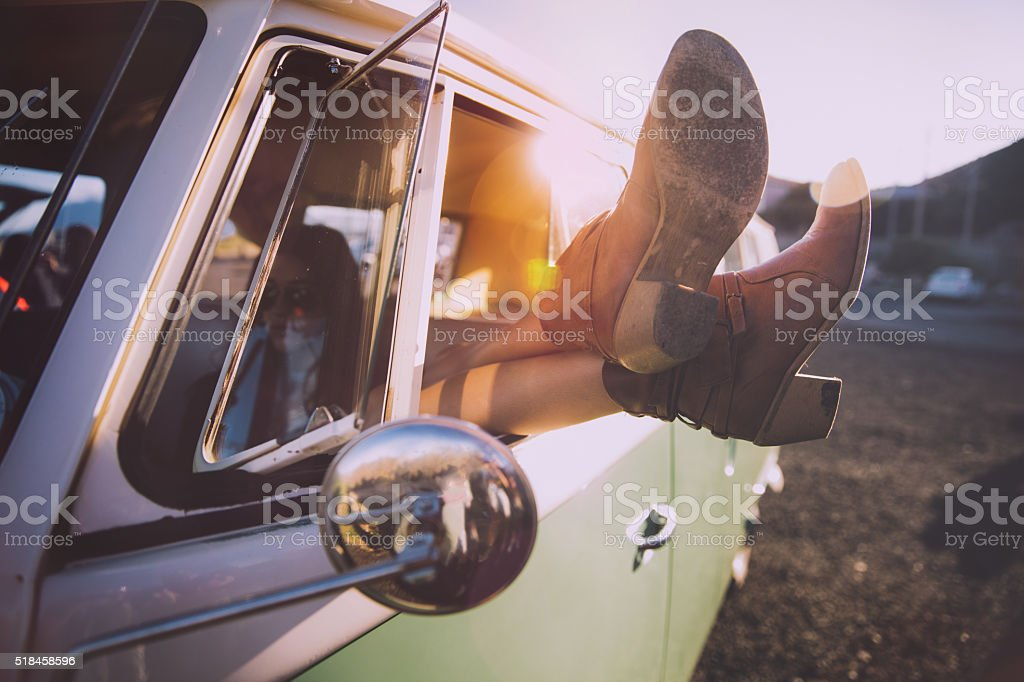 Young woman relaxing during a road trip with vintage van stock photo