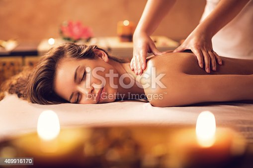 istock Young woman relaxing during back massage at the spa. 469916170
