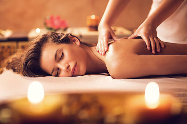 young woman relaxing during back massage at the spa. - menselijke rug stockfoto's en -beelden