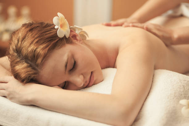 young woman relaxing during back massage at the spa - thai massage stock photos and pictures