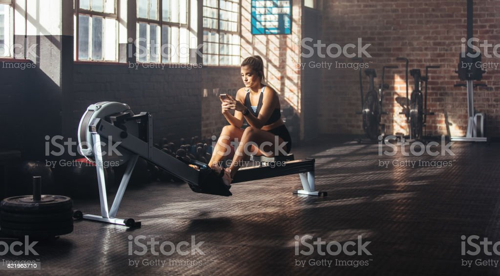 Young woman using phone while training at the gym. Woman sitting on...