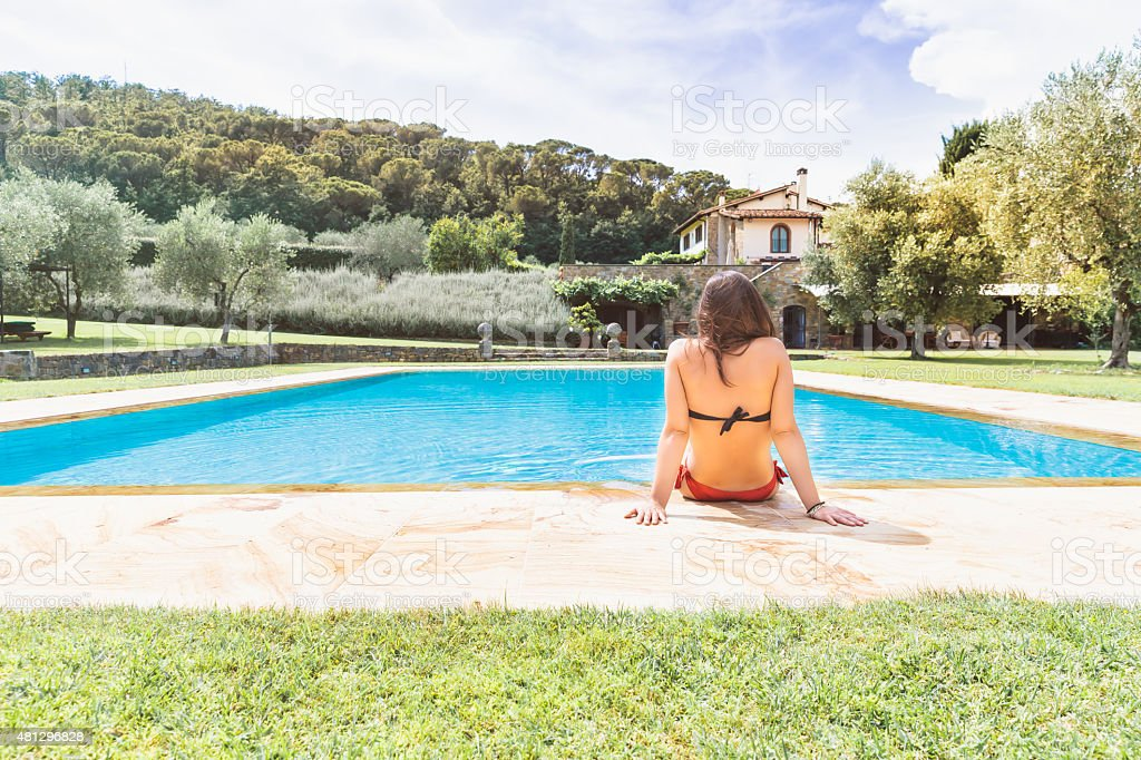 Young woman relaxing in a resort swimming pool stock photo