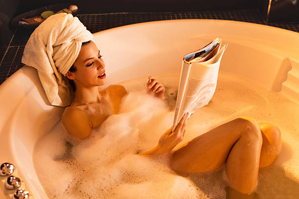 young woman relaxing in bathtub and reading a magazine. - woman home magazine stockfoto's en -beelden