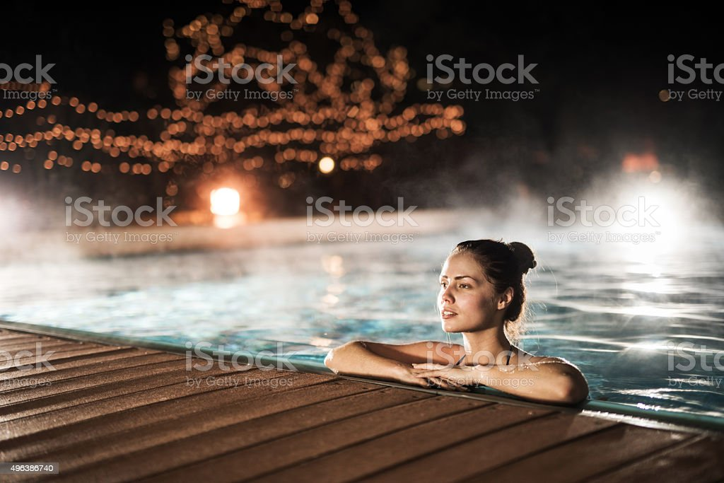 Young woman relaxing in heated swimming pool during winter night. stock photo