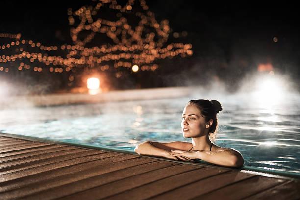젊은 여자 저녁에 온수 수영장 겨울 동안 있습니다. - 헬스 스파 뉴스 사진 이미지