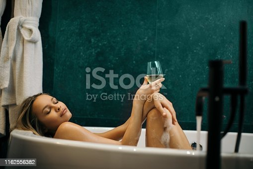 Beautiful and attractive young woman with long blonde hair relaxing in hot bath while holding glass with white wine