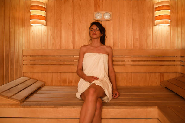 Young woman relaxing in sauna at health spa Young woman relaxing in sauna at health spa. sauna stock pictures, royalty-free photos & images