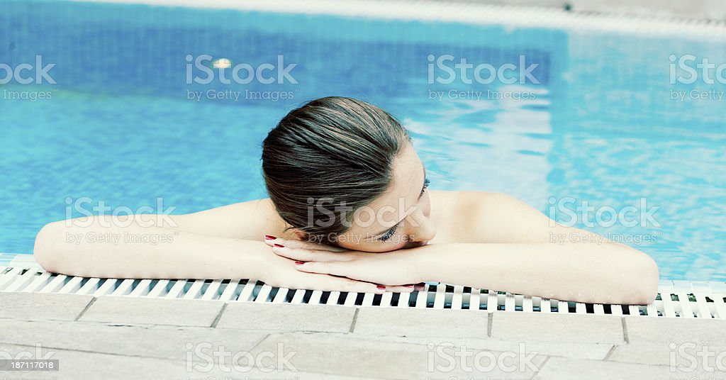 young woman relaxing in swimming pool stock photo