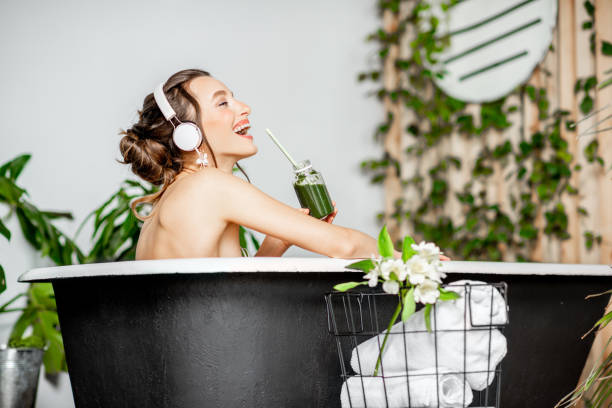 Young woman relaxing in the bathtub Young relaxed woman listening to the music and drinking smoothie while lying in the retro bathtub at the beautiful bathroom with green plants bathtub stock pictures, royalty-free photos & images