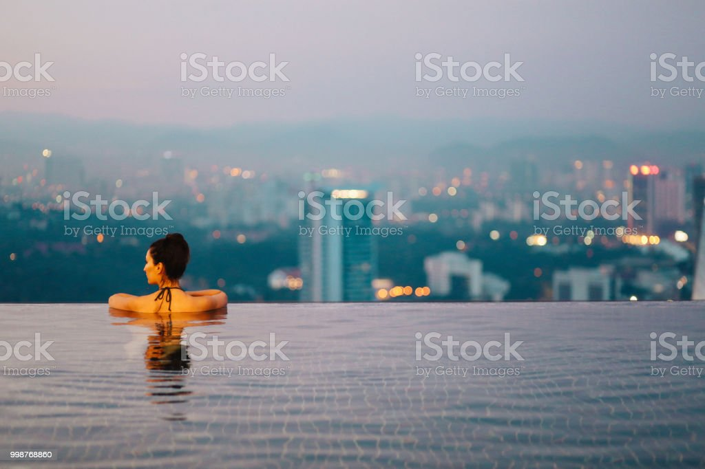 Young woman relaxing in the pool as the sun sets above Kuala Lumpur stock photo
