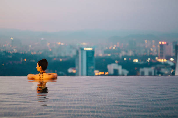 Young woman relaxing in the pool as the sun sets above Kuala Lumpur Young brunette woman relaxing in the pool, swimming on top of the building in Kuala Lumpur, Malaysia. She is having a moment to relax after work in the busy city of Kuala Lumpur, Malaysia. infinity pool stock pictures, royalty-free photos & images