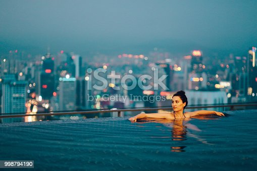 Young brunette woman relaxing in the pool, swimming on top of the building in Kuala Lumpur, Malaysia. She is having a moment to relax after work in the busy city of Kuala Lumpur, Malaysia.