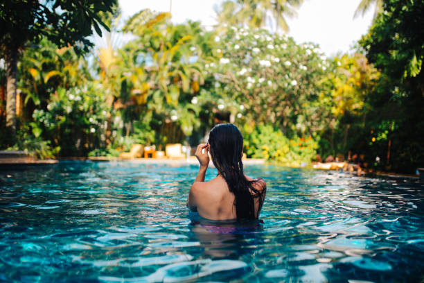 Young woman relaxing in the pool stock photo
