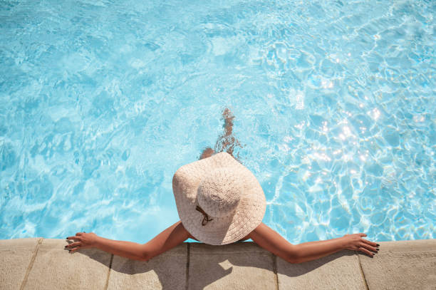Young woman relaxing in the swimming pool stock photo