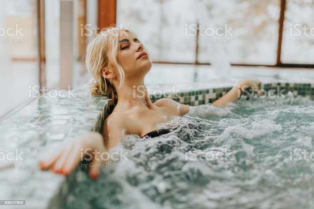 Young woman relaxing in the whirlpool bathtub stock photo