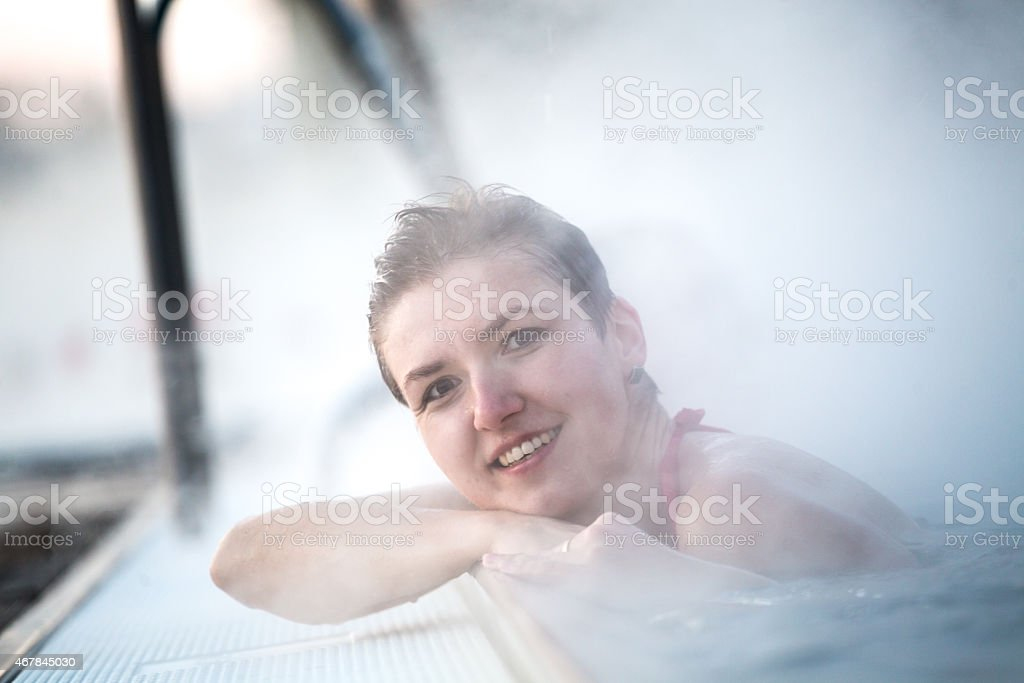 Young woman relaxing in thermal pool. stock photo