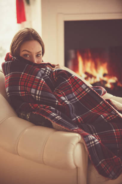 Young woman relaxing next to a fireplace Shot of young woman relaxing in her living room next to a fireplace, wrapped in a cozy blanket on a cold winter's day. She is looking at camera. wrapped in a blanket stock pictures, royalty-free photos & images