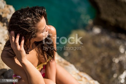 468906855 istock photo Young woman relaxing on a beautiful beach 1178585430