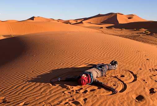 istock Young woman relaxing on a dune in Sahara desert in a late afternoon 988281650